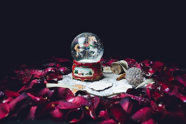 Rote rosenblätter umgeben weihnachtsglaskugel mit schnee