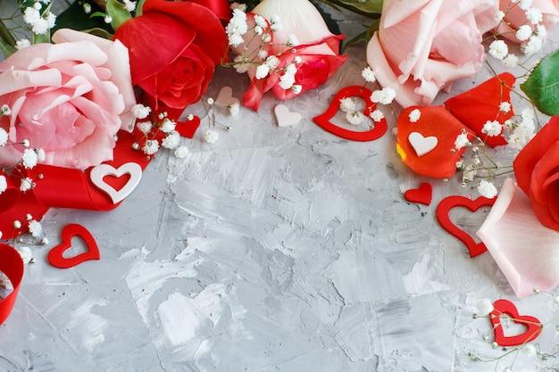 Rote rosenblumen, blütenblätter und herzen auf grauem hintergrund
