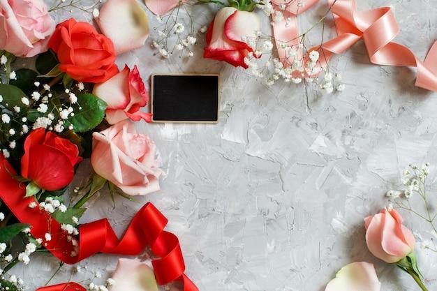 Rote rosenblumen, blütenblätter und kleine tafel auf grauem hintergrund