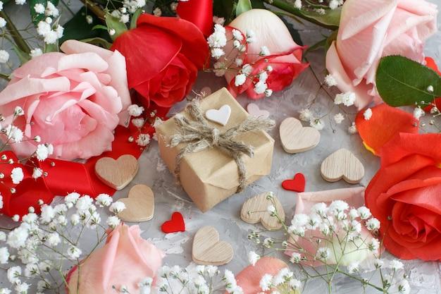 Rote rosenblumen und geschenkbox mit herzen auf grauem hintergrund