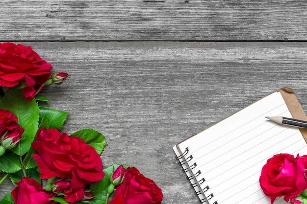 Rote rosenblumen und leeres gezeichnetes notizbuch auf rustikalem hölzernem hintergrund