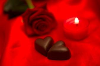 Rote Rosenkerze und Schokoladenherzen