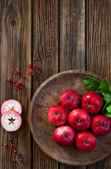 Rote saftige äpfel in einer rustikalen hölzernen schüssel der weinlese