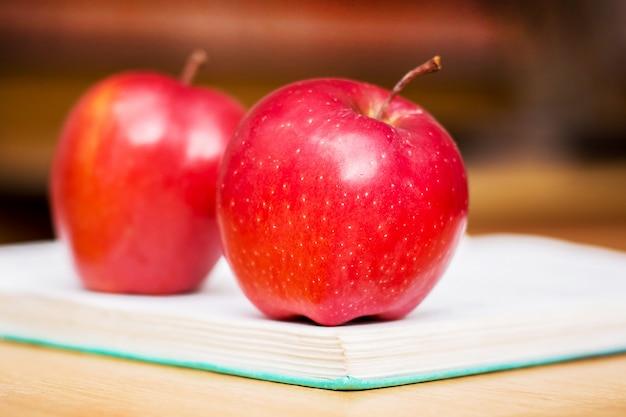 Rote saftige äpfel liegen auf einem buch im büro