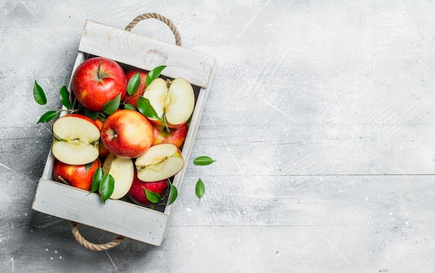Rote saftige äpfel und apfelscheiben in einer holzkiste.