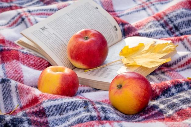 Rote saftige äpfel und ein gelbes ahornblatt nahe einem offenen buch im wald