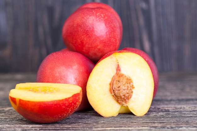 Rote saftige nektarinen, von denen einige in scheiben geschnitten sind, nahaufnahme von essen auf dem tisch