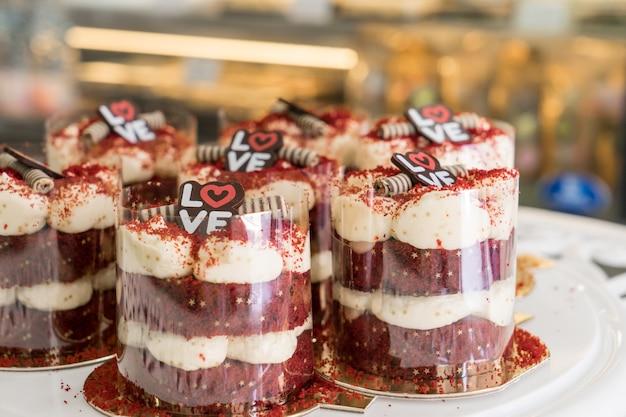Rote samtkleine kuchen mit sahne draufsicht der käsereisung im bäckereishop