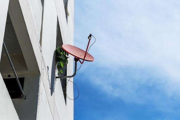 Rote satellitenschüssel auf turm mit blauem himmel