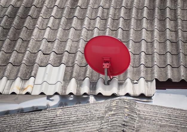 Rote satellitenschüssel ist auf dem dach angebracht. bangkok, thailand.