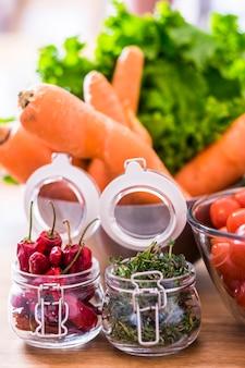 Rote scharfe chilischote und grüne heilkräuter mit frischem saisongemüse - vegetarische und vegane gesundheitskost für wellness- und diätkonzept