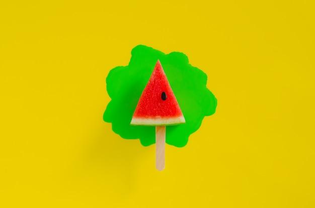 Rote scheibe wassermelonenentwurf als eiscreme mit stock, die grünen plakatfarbentropfen auf gelbem hintergrund haben. minimales sommerfruchtkonzept.