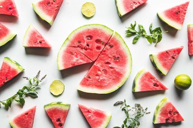 Rote scheiben der reifen wassermelone mit minzblättern und limettenscheiben auf einem weißen hintergrund. draufsicht, flach liegen