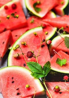 Rote scheiben köstlicher saftiger wassermelone mit walderdbeeren, die auf einem grauen tisch liegen