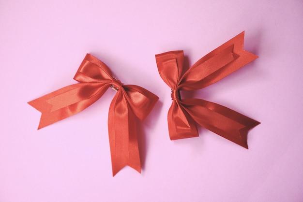 Rote schleife auf rosa. geschenkbogen haarnadel perfekte urlaub handgemacht