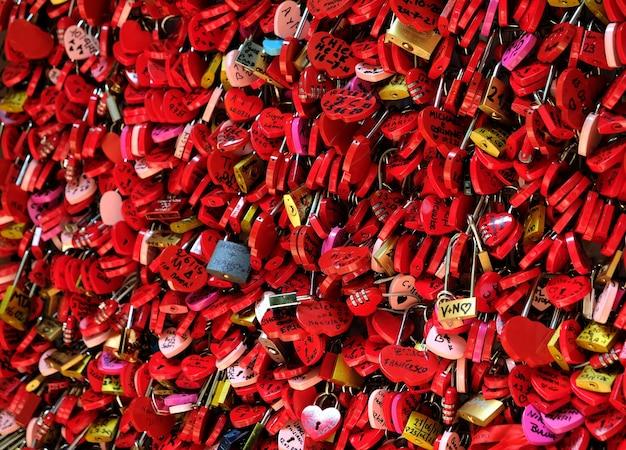 Rote schlösser in herzform an einem zaun