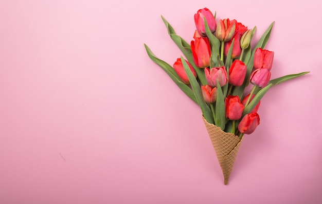 Rote schöne tulpen in einem eiswaffelkegel einen farbhintergrund. konzeptionelle idee eines blumengeschenks. frühlingsstimmung
