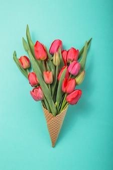 Rote schöne tulpen in einer eiscreme-waffelkegel auf einem blauen hintergrund der farbe. konzeptionelle idee eines blumengeschenks. frühlingsstimmung