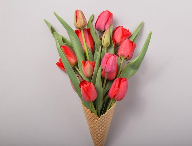 Rote schöne tulpen in einer eiscreme-waffeltüte auf einem konkreten hintergrund. konzeptionelle idee eines blumengeschenks. frühlingsstimmung