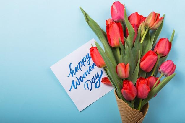 Rote schöne tulpen in einer eiscreme-waffeltüte mit frauentag der karte auf einem farbhintergrund. konzeptionelle idee eines blumengeschenks. frühlingsstimmung