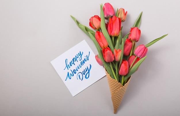 Rote schöne tulpen in einer eiscreme-waffeltüte mit frauentag der karte auf einem konkreten hintergrund. konzeptionelle idee eines blumengeschenks. frühlingsstimmung
