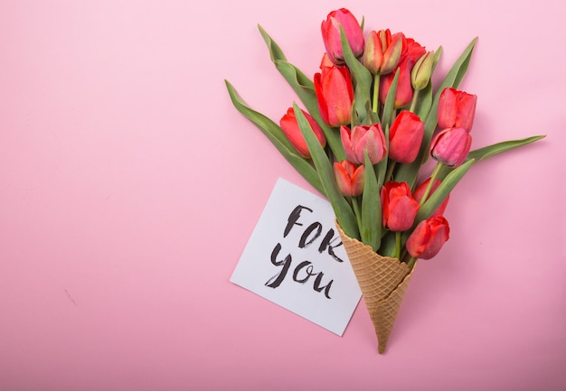 Rote schöne tulpen in einer eiscreme-waffeltüte mit karte auf einem farbhintergrund. konzeptionelle idee eines blumengeschenks. frühlingsstimmung