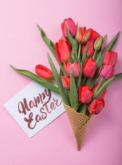Rote schöne tulpen in einer eiscreme-waffeltüte mit karte frohe ostern auf einem farbigen hintergrund. konzeptionelle idee eines blumengeschenks. frühlingsstimmung
