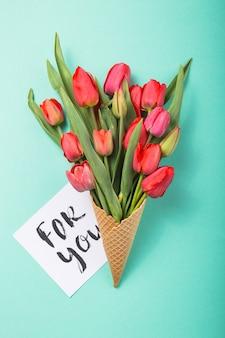 Rote schöne tulpen in einer eiscreme-waffeltüte mit karte für sie auf einem farbigen blauen hintergrund. konzeptionelle idee eines blumengeschenks. frühlingsstimmung