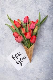 Rote schöne tulpen in einer eiscreme-waffeltüte mit karte für sie auf einem konkreten hintergrund. konzeptionelle idee eines blumengeschenks. frühlingsstimmung