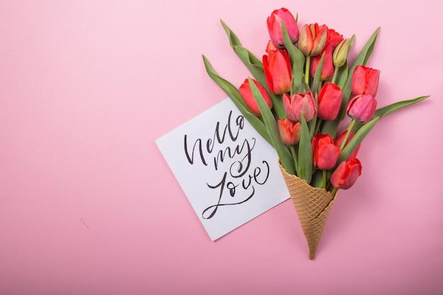 Rote schöne tulpen in einer eiscreme-waffeltüte mit karte hallo meine liebe auf einem farbhintergrund. konzeptionelle idee eines blumengeschenks. frühlingsstimmung
