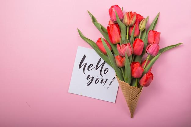 Rote schöne tulpen in einer eiscreme-waffeltüte mit karte hallo sie auf einem farbhintergrund. konzeptionelle idee eines blumengeschenks. frühlingsstimmung