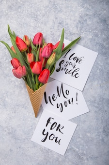 Rote schöne tulpen in einer eiscreme-waffeltüte mit karte hallo sie auf einem konkreten hintergrund. konzeptionelle idee eines blumengeschenks. frühlingsstimmung