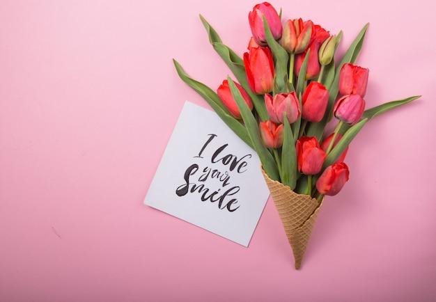Rote schöne tulpen in einer eiscreme-waffeltüte mit karte ich liebe ihr lächeln auf einem farbigen hintergrund. konzeptionelle idee eines blumengeschenks. frühlingsstimmung