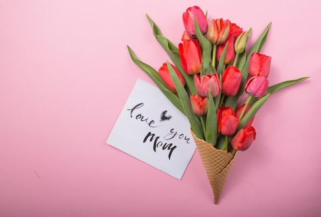 Rote schöne tulpen in einer eiscreme-waffeltüte mit karte liebe dich mama auf einem farbhintergrund. konzeptionelle idee eines blumengeschenks. frühlingsstimmung