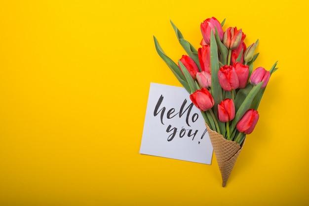 Rote schöne tulpen in einer eiscreme-waffeltüte mit tintenkarte auf gelbem farbhintergrund. konzeptionelle idee eines blumengeschenks. frühlingsstimmung