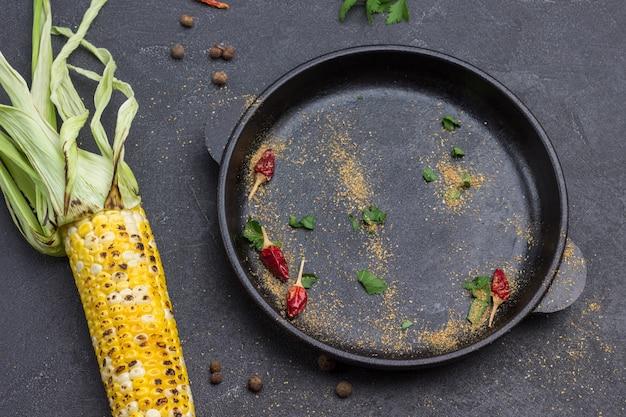 Rote schoten, gemahlenen koriander und petersilienblätter in einer pfanne trocknen. gegrillter mais und zwei kalkhälften auf dem tisch. schwarzer hintergrund. ansicht von oben