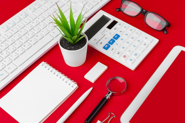 Rote schreibtischtabelle mit leerem notizbuch, tastatur und versorgungen. draufsicht mit kopienraum. flach liegen.