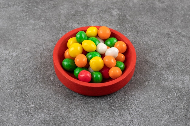 Rote schüssel der bunten runden bonbons auf steintisch.