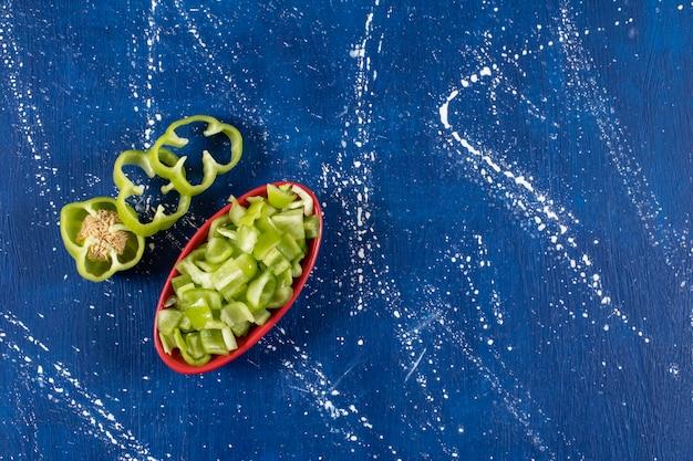 Rote schüssel mit frischen grünen paprikaringen auf marmoroberfläche.