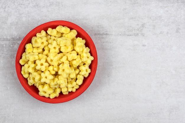 Rote schüssel voll köstlicher cornflakes auf steintisch.