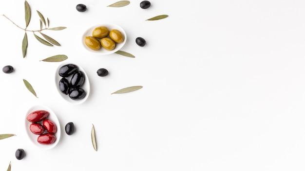 Rote schwarze gelbe oliven auf platten mit kopienraum