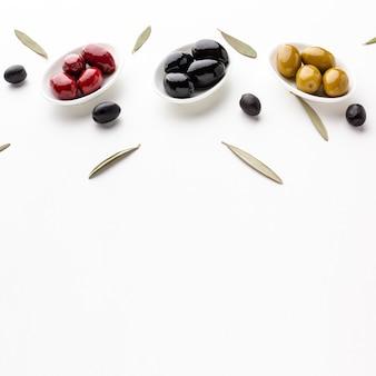 Rote schwarze gelbe oliven des hohen winkels auf platten