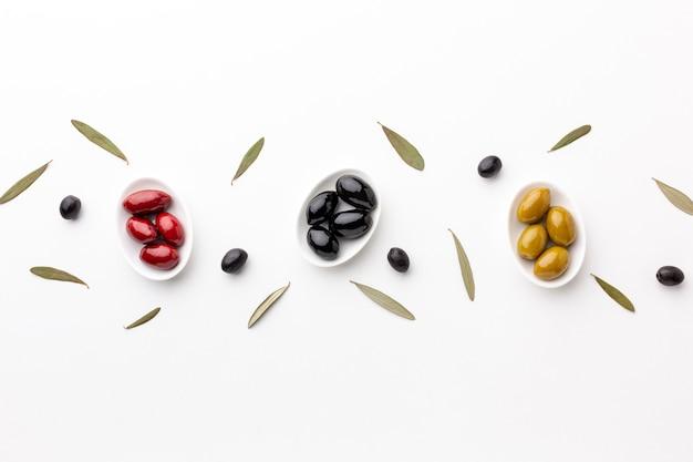 Rote schwarze grüne oliven auf platten