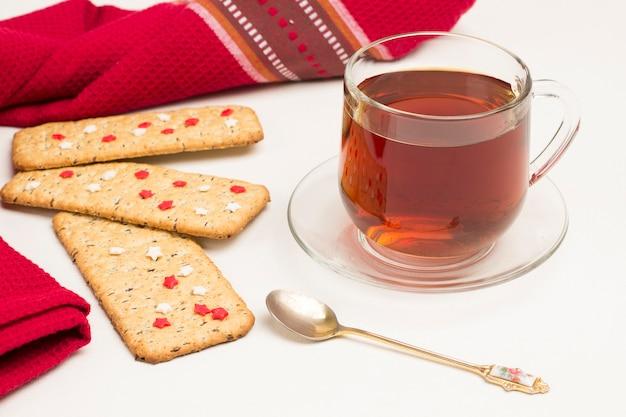 Rote serviette des weihnachtslebkuchenplätzchens und tasse tee auf weißem hintergrund