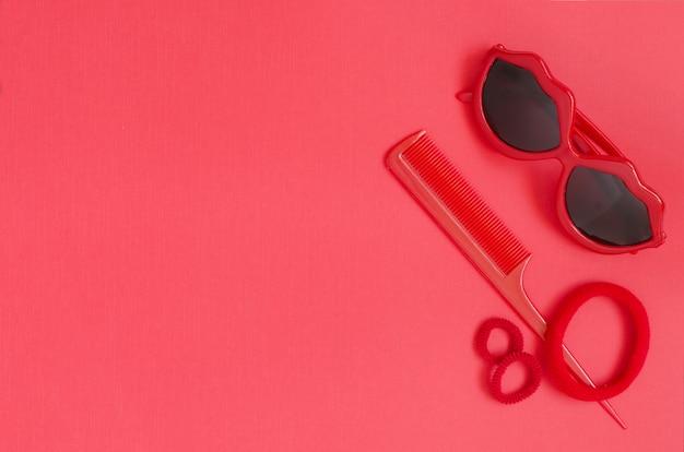 Rote sonnenbrille, kamm, haargummibänder. roter hintergrund