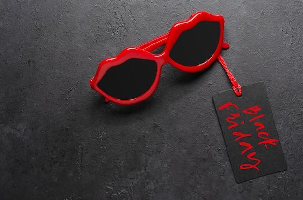 Rote sonnenbrille. schwarzer freitag - handschriftliche inschrift auf dem etikett.