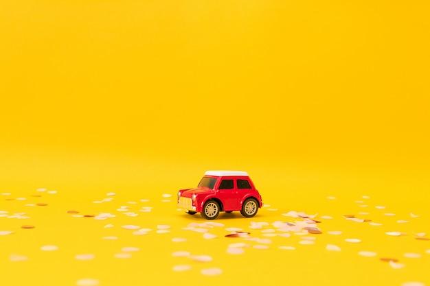 Rote spielzeugmaschine auf gelbem grund. minimale feiertagsgrußkarte mit kopienraum.