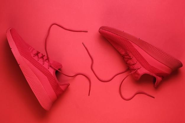 Rote sportlaufschuhe mit ungebundenen schnürsenkeln auf rotem hintergrund