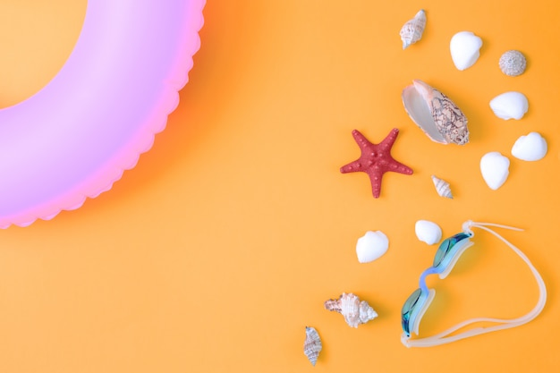 Rote starfish und verschiedene shells auf hellem orange hintergrund.