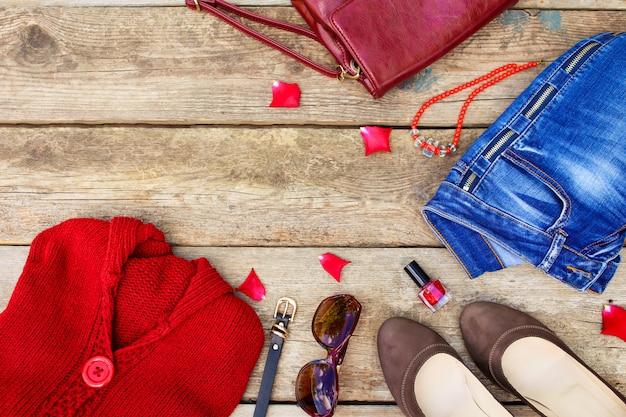 Rote strickjacke der herbstkleidung und -zubehörs der frauen, jeans, handtasche, perlen, sonnenbrille, nagellack, schuhe, gurt auf hölzernem hintergrund. ansicht von oben.